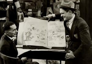 Photograph of cartoonist George Herriman and actor Glenn Tryon seated around comic sketches
